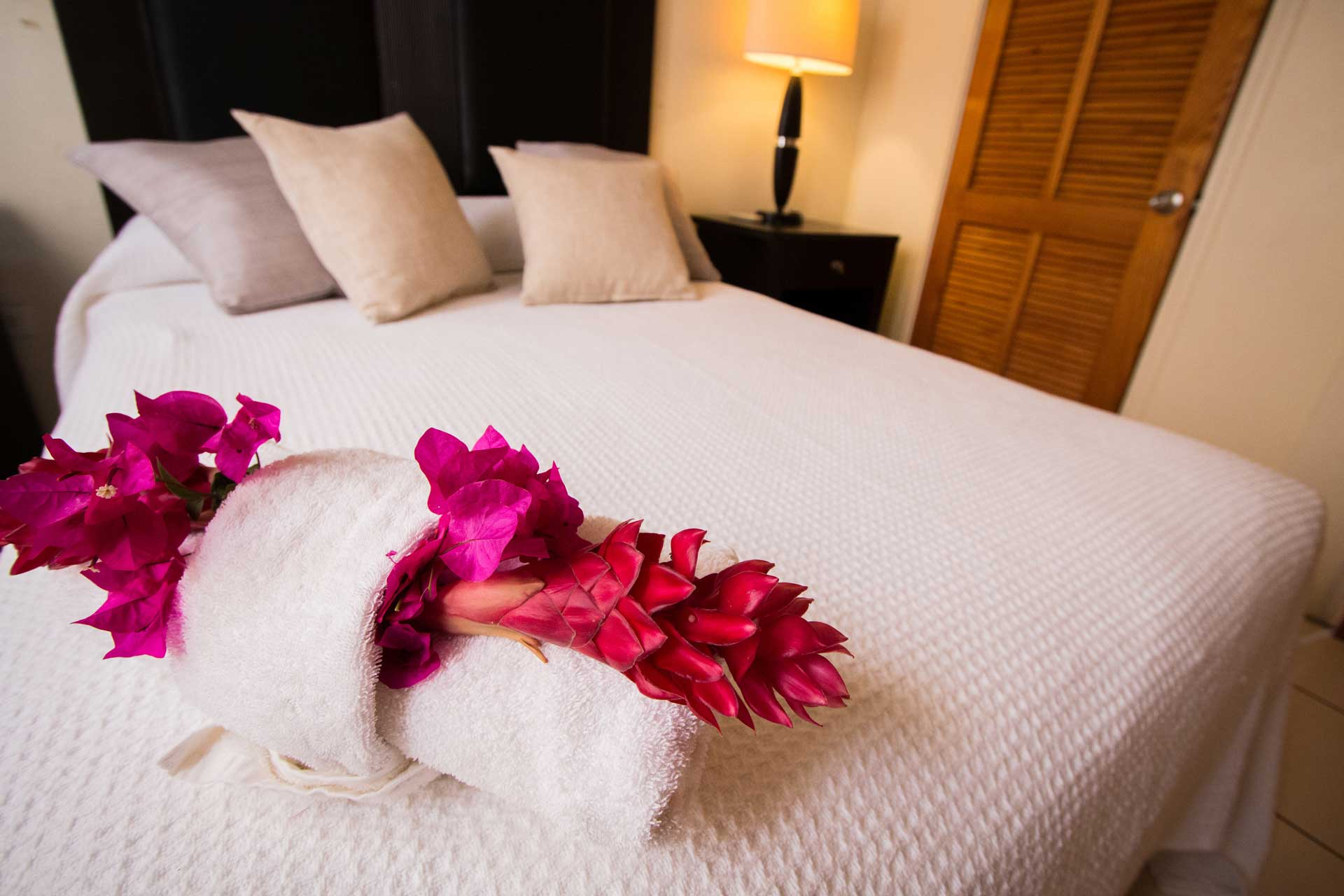 Connies Comfort Suites bed with flowers and towel